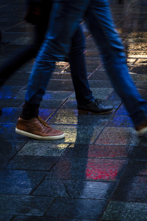 People walking in the reflection of neon lights on the wet sidewalk in wintertime. Stock Photo