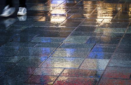 waist down: Walking in the reflection of neon lights on the wet sidewalk in wintertime.