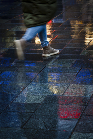Girl walking in the reflection of neon lights on the wet sidewalk. Stock Photo