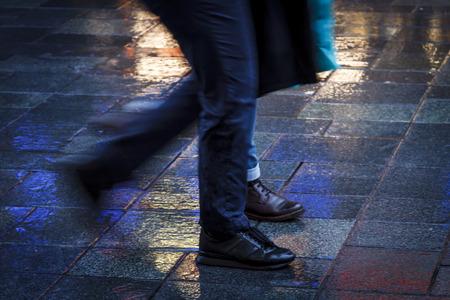 waist down: People walking in the reflection of neon lights on the wet sidewalk.