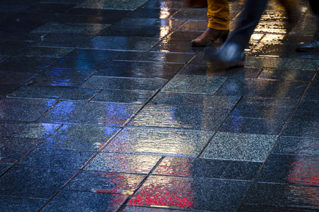 Two people walking in the reflection of neon lights on the wet sidewalk. Stock Photo