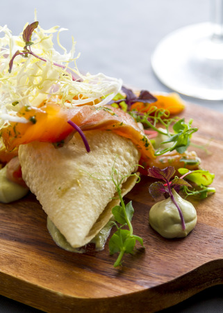 Fresh healthy salmon salad displayed on a wooden serving board. Stock Photo