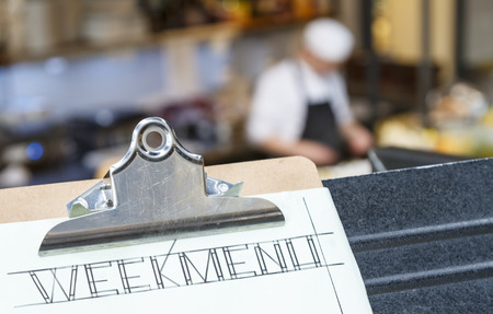 Week menu clipboard with restaurant and cook in the background.