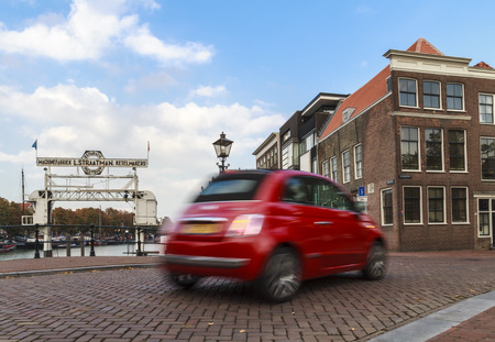 swerving: DORDRECHT, NETHERLANDS - OCTOBER 9 2015: Shiny red Fiat 500 with motion blur driving in the old center of Dordrecht.