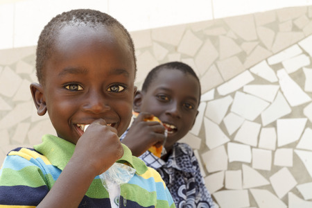 SENEGAL, AFRICA - APRIL 24 2016: Two unidentified bright-eyed Senegalese kids eating snacks during a visit to their village.