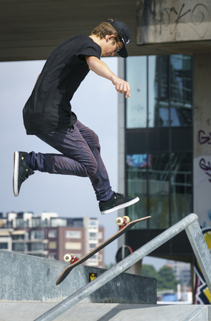 DORDRECHT, NETHERLANDS - 3 SEPTEMBER 2016: Young skateboarder jumping during the warm-up at the official opening of the new skateboard park in Dordrecht.