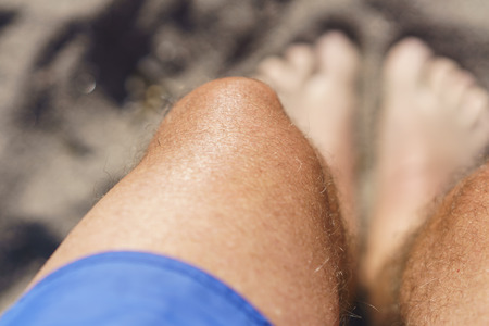 Looking down at my feet on the beach while wearing shorts