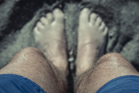 Looking down at my feet on the beach with my knees in focus