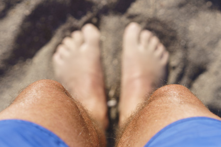 Looking down at my feet on the beach while with toes in the sand