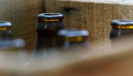 Old beer bottles in a wooden crate on display outside a shop. Stock Photo