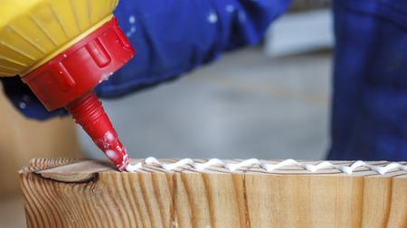 Carpenter en el trabajo usando pegamento en su taller. Foto de archivo