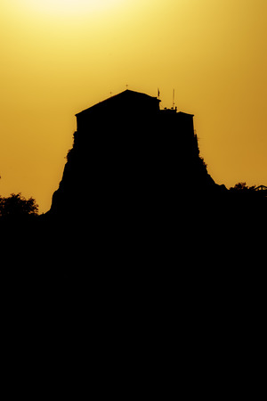 Church of Virgin Mary in Petra on Lesvos at sunset producing a golden silhouette.