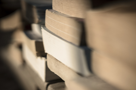 Many old paperback books by the beach held down with stones from the wind. Depth of field. Stock Photo