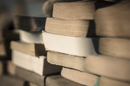 Piles of old paperback books by the beach held down with stones from the wind. Stock Photo