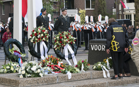 DORDRECHT - THE NETHERLANDS - MAY 4 2017: Members of Amnesty International in Dordrecht laying flowers at war monument on Sumatraplein on the National Remembrance Day.