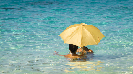 Two young asian women under an umbrella standing in the turquoise sea 5