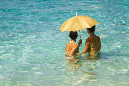 Two young asian women under an umbrella standing in the turquoise sea 4