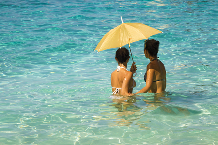 Two young asian women under an umbrella standing in the turquoise sea 3