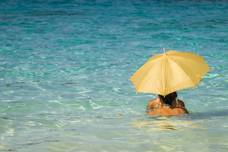 Two young asian women under an umbrella standing in the turquoise sea 2 Stock Photo