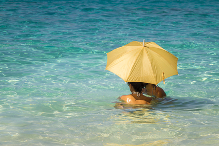 Two young asian women under an umbrella standing in the turquoise sea 1