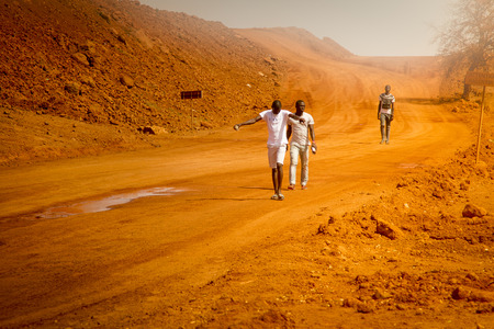 SENEGAL, AFRICA - APRIL 26 2016: Unidentified young Senegalese men walking home after working on a new road in Senegal.