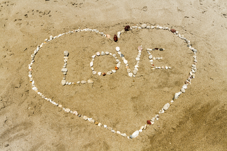 Word love and heart shape made from pebbles on a sandy beach