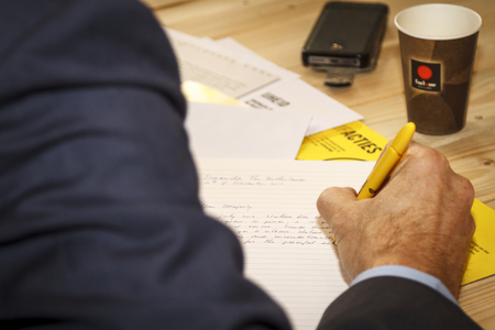 Dordrecht, The Netherlands - December 10, 2015: Man writing a letter during a letter-writing campaign organized in Dordrecht library by Amnesty International.