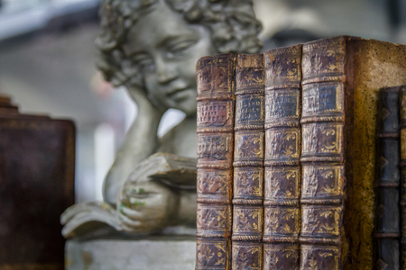 Statue of angel leaning and reading next to old brown books on a bookshelf
