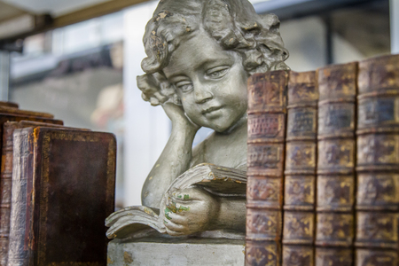 Angelic statue and old brown books on a bookshelf