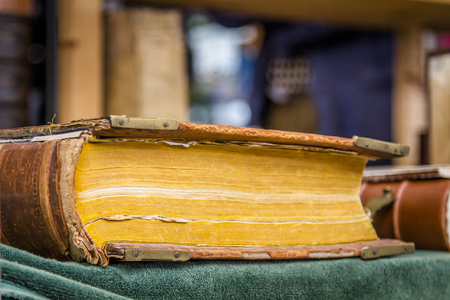Ancient bound  book with yellowing pages lying on table covered by green carpet