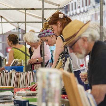 DORDRECHT, NEDERLAND - JULI 7 2013: Mensen die zich bij een boekenkraam bevinden die wat beslissen om bij de jaarlijkse die boekhandel te kopen in het centrum van Dordrecht wordt gehouden. De markt trekt jaarlijks 75.000 bezoekers.