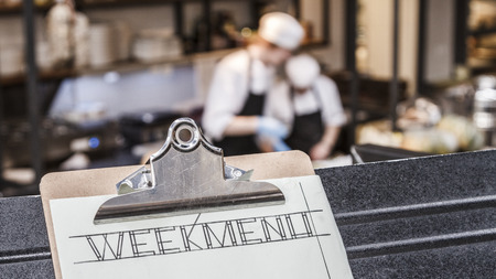 Week menu clipboard with restaurant kitchen and two cooks busy in the background. Stock Photo