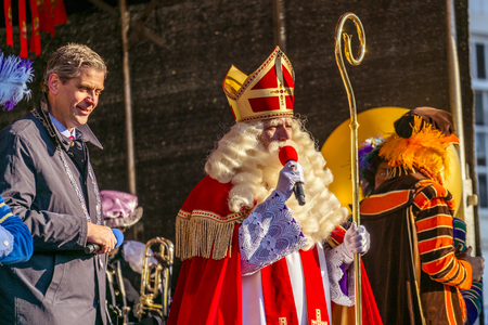 Dordrecht, Netherlands - November 17, 2018: Saint Nicolaas on stage speaking to the children with the mayor of Dordrecht, Wouter Kolff, standing by his side Redactioneel