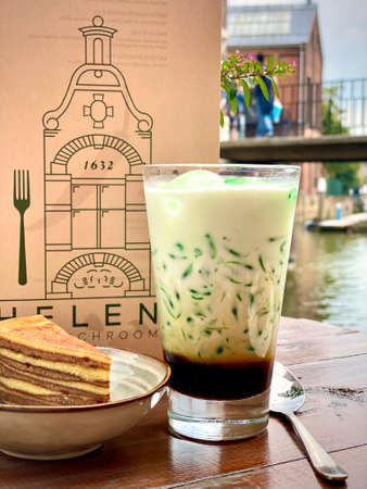 Traditional Indonesian sweet refreshing drink cendol made from pandas juice, mung bean. Restaurant cafe wooden table outside outdoors. Served drink in glass with a slice of layer cake in a bowl with a menu in background. Colorful green, brown creamy drink. Thirst-quenching thirsty.