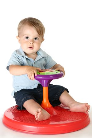Adorable 1 year old  boy playing with spinning toy.