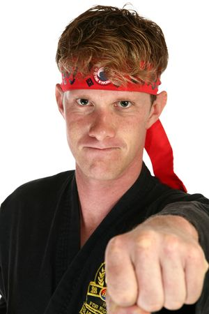 30 something: Attractive 30 something man in martial arts uniform punching towards camera.