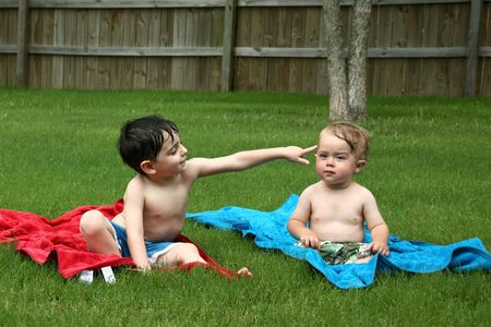 Two toddler boys sitting on towels in their swim suits in the grass.