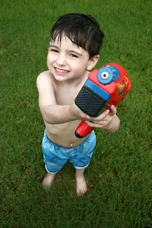 Adorable four year old boy playing with water gun outside in grass. 免版税图像