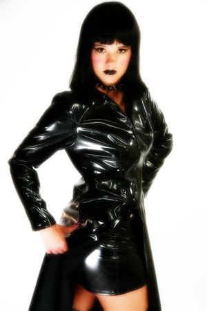 Beautiful thirty year old brunette in black vinyl costume.