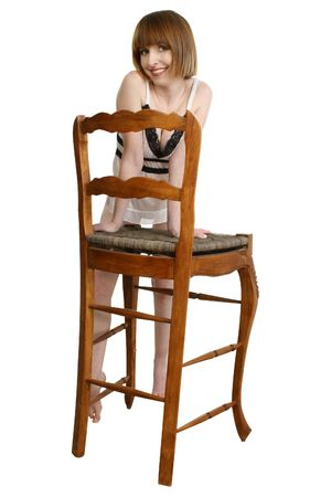 thirty something: Thirty something woman in lingerie leaning on chair over white. Stock Photo