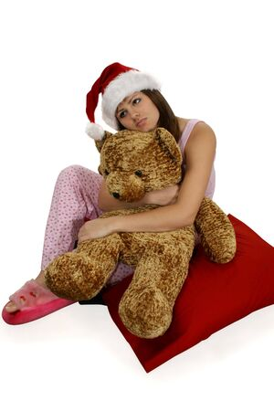 pjs: Teen girl day dreaming. Sitting in pjs, wearing santa hat and holding stuffed bear.  Clipping path included.