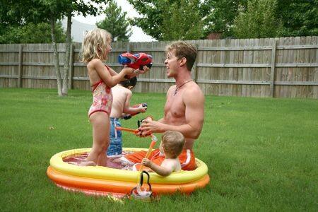 kiddie: Boys and Girl with Dad in the kiddie pool. Stock Photo