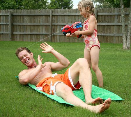 watergun: Backyard fun as girl squirts dad with watergun Stock Photo