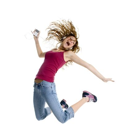 Beautiful teen girl jumping while listening to digtial music player.