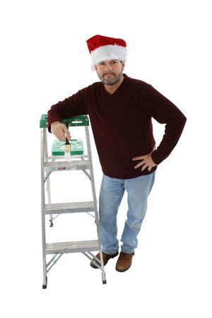하얀 페인트 브러시로 사다리에 기대어 산타 모자에있는 남자