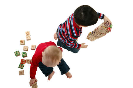Brother and sister playing with blocks over white background.