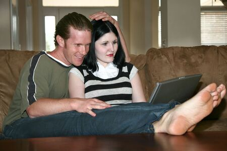 Casual couple sitting on couch at home with laptop. photo