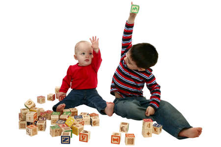 Toddler boy and girl playing with alphabet blocks over white.  photo
