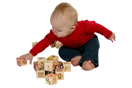 Adorable toddler girl playing with alphabet blocks over white. photo
