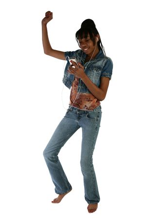 Beautiful African American teen girl dancing to digital music player over white background.